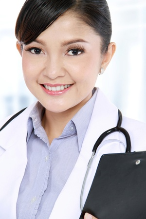 Close up of attractive woman doctor with a clipboard on office photo