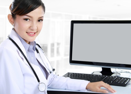 smiling doctor woman sitting on her office with computer set on her table photo