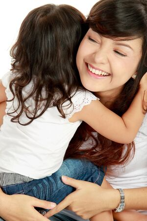 two girls hugging: Smiling embracing mom and daughter isolated over white background
