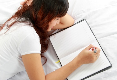 hand holding pen: Closeup portrait of a relaxed young girl writing book while lying on the bed