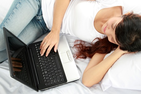 Top view of happy girl lying in bed with laptop photo