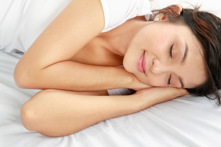 Top view image of a lovely young female sleeping on the bed photo