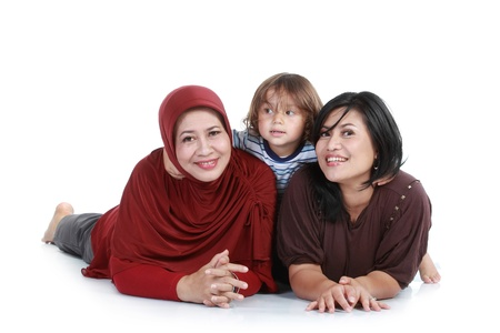 muslim baby girl: happy muslim family lying on floor. isolated over white background