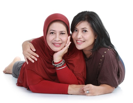 east asian ethnicity: muslim woman with her daughter  lying on isolated over white backround