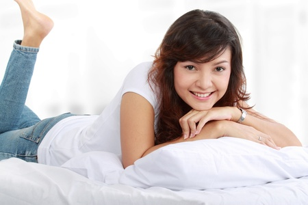 sweet smile: portrait of a happy young lady lying on the bed Stock Photo