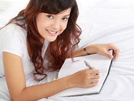 home planning: Closeup portrait of a smiling young girl writing book while lying on the bed