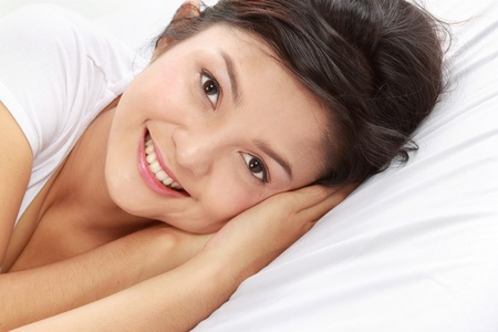 lifestyle looking lovely: lovely young female lying on the bed looking at camera Stock Photo