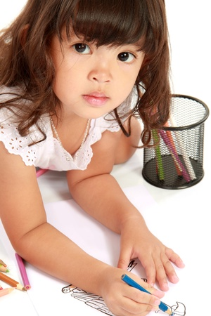 Girl sitting on floor and making drawings on paper over white background photo