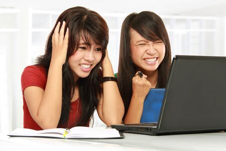 two disappointed young expressive student girl work on laptop Stock Photo - 11845989