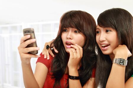 Two surprise girls reading text message in mobile phone Stock Photo - 11846698