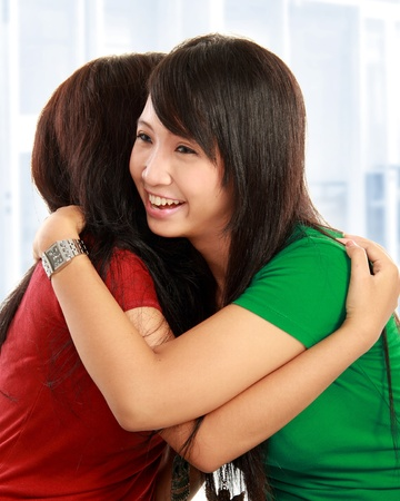 two friends: happy asian women hugging each other and smiling Stock Photo