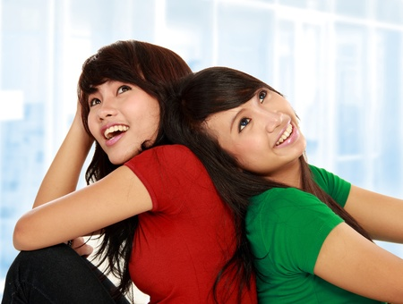 best friends girls: portrait of two young asian female looking up thinking something Stock Photo