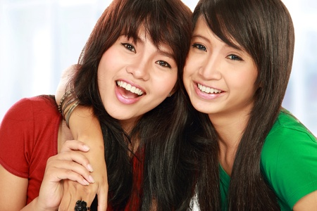 teenage girls: close up portrait of attractive two teenage girls hugging each other