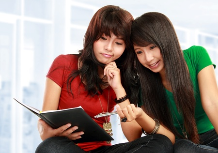 Portrait of a young students smiling while reading a book Stock Photo - 11847293