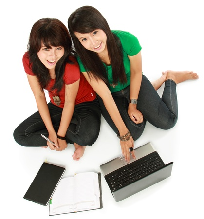 top view of Two girls-students with laptop sitting on white background photo