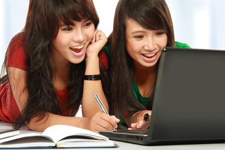 two young attractive girl laughing while using laptop photo