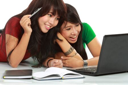 two asian young attractive girl laughing while using laptop Stock Photo - 11846944