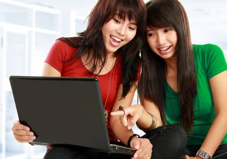 Two pretty women learning with a laptop Stock Photo - 11847113