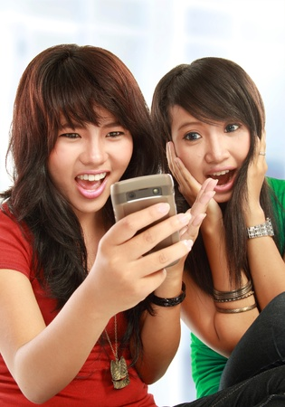 Two surprise girls reading text message in mobile phone photo