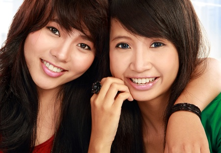 close up portrait of attractive two teenage girls hugging each other photo