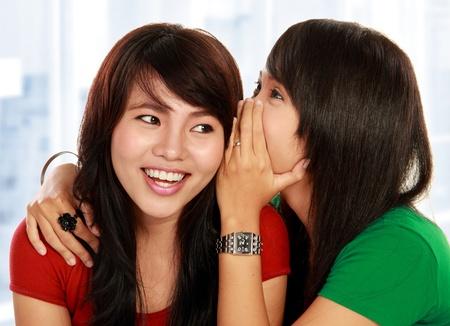 habladur�as: dos mujer asi�tica joven susurrando un chisme Foto de archivo