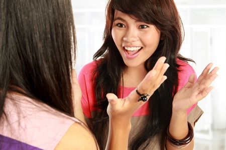 discussing: two young asian woman having a conversation Stock Photo