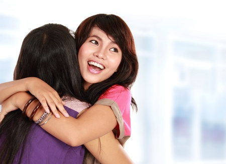 embraces: happy asian women hugging each other and smiling Stock Photo