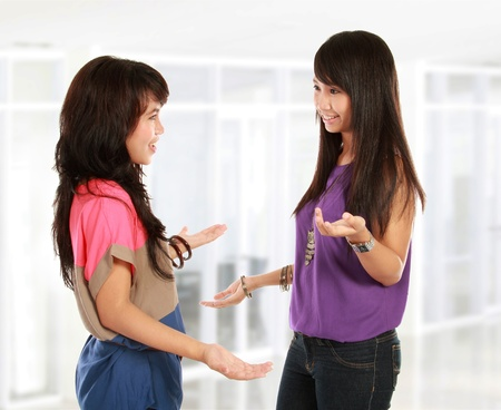 two women talking: two young asian woman having a conversation Stock Photo