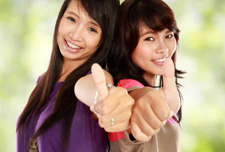 fingers on top: two young asian girl showing thumb up sign over a bokeh background