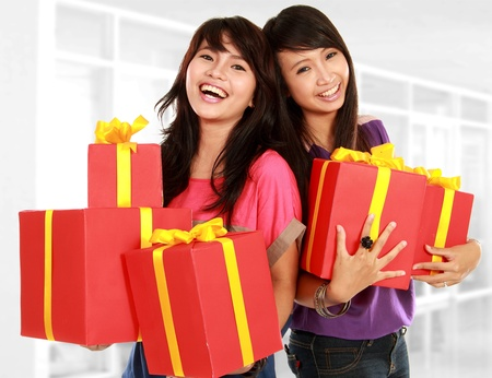 two young girls smiling while carrying present photo