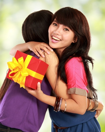 young asian woman hugging her friend for giving her a present photo
