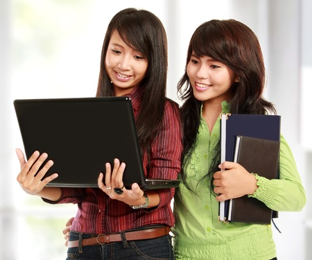 Two pretty women learning with a laptop Stock Photo - 11844272