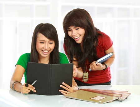 studygroup: Portrait of a young students smiling while reading something