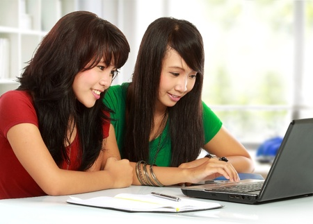 two young attractive girl smiliing while browsing the internet Stock Photo - 11844998