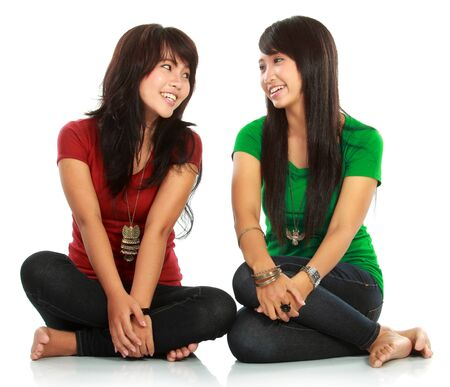 portrait of attractive two girls laughing looking each other on white background