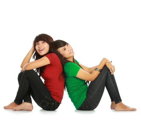best friends: portrait of two young asian female looking up thinking something on white background