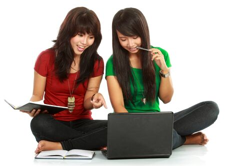 Two girls-students with laptop sitting on white background Stock Photo - 11846120