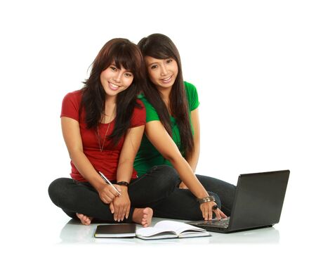 Two girls-students with laptop sitting on white background photo