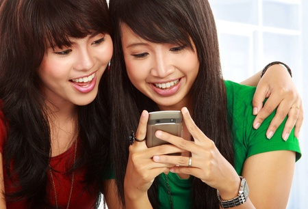 young asian woman smiling reading a text message on mobile phone photo
