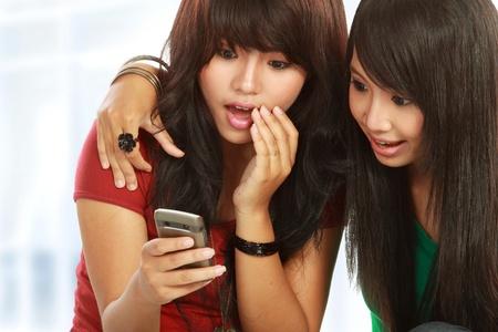 gossip: verbaasde meisjes het lezen van roddels in mobiele telefoon Stockfoto
