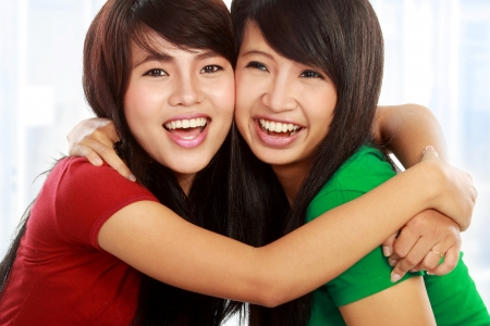 close up portrait of attractive two best friend hugging each other
