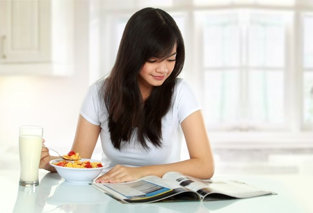 young woman having breakfast while reading magazine photo