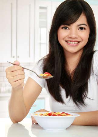 young pretty woman having a bowl of cereal for her breakfast Stock Photo - 12004834