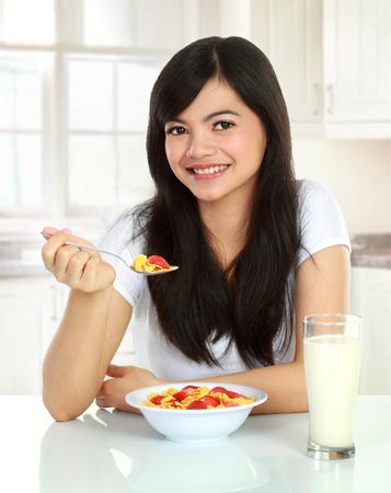 young pretty woman having a bowl of cereal with milk for her breakfast Stock Photo - 12004797