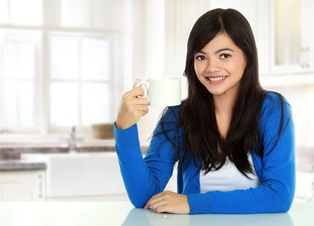 portrait of Pretty asian woman having a glass of tea while breakfast photo