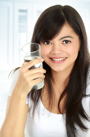 Healthy young woman holding a glass of water and smiling photo