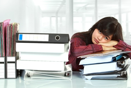 going crazy: young business woman with many paper work stressed at work