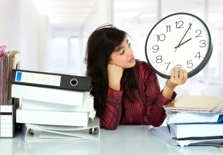 young business woman with many paper work and big clock stressed at work photo