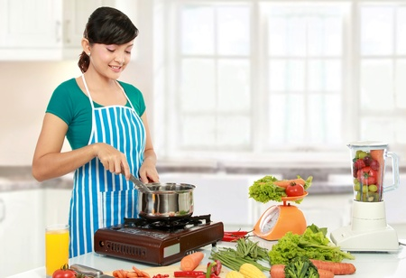 woman cooking: Beautiful woman cooking something in the kitchen Stock Photo
