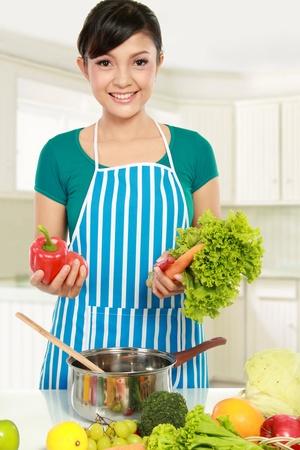 ama de casa: mujer sonriente poner un mont�n de ingredientes saludables en un recipiente de cocci�n Foto de archivo